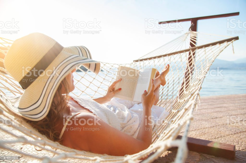 Young woman, reading a book in a hammock at sunset. stock photo