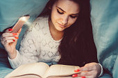 Woman using smartphone to read book under the blanket