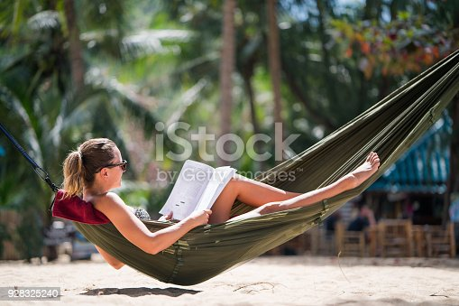 Relaxed woman sunbathing in hammock on the beach and reading a book.