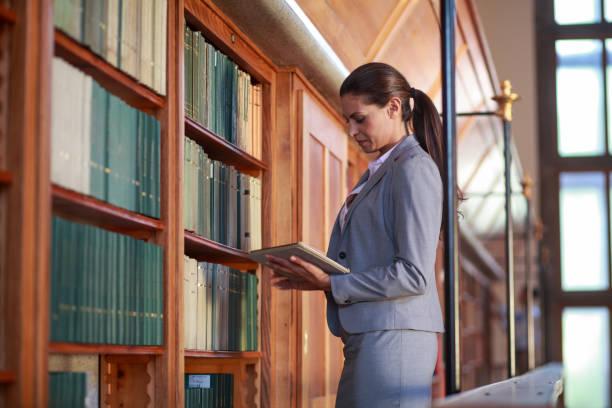 Junge Frau liest ein Buch in der öffentlichen Bibliothek – Foto