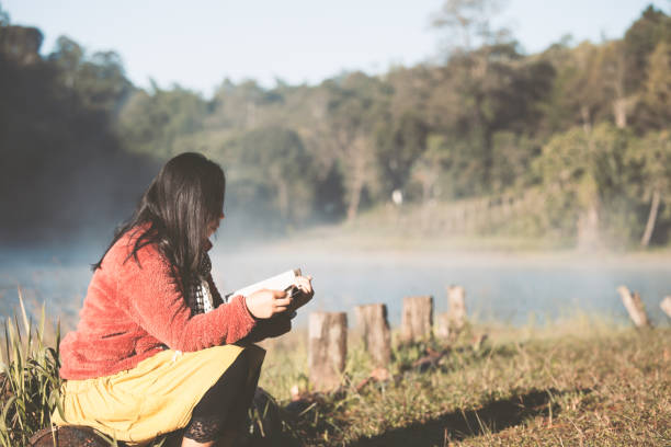 Young woman reading a book in the nature park with freshness in the morning with sunlight stock photo