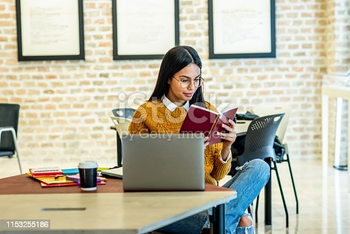 istock young woman reading a book in the office 1153255186