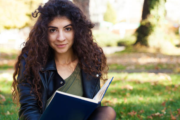 Young woman reading a book in the park stock photo