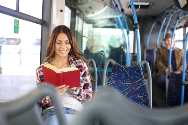 Junge Frau liest ein Buch im Bus – Foto