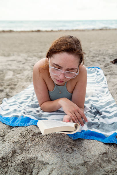 Young woman reading a book on the beach. stock photo