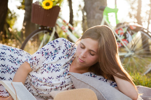 Young woman reading a book outdoors stock photo