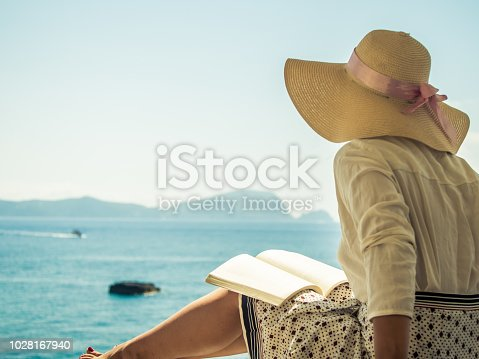 Young woman reading a book sitting on wooden balcony on Palmarola island in front of the ocean on a sunny day. Elegant white dress with skirt and hat.