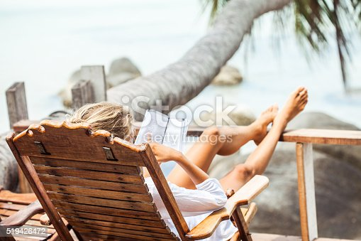 538041934 istock photo Young woman reading a book while relaxing on tropical island 519426472