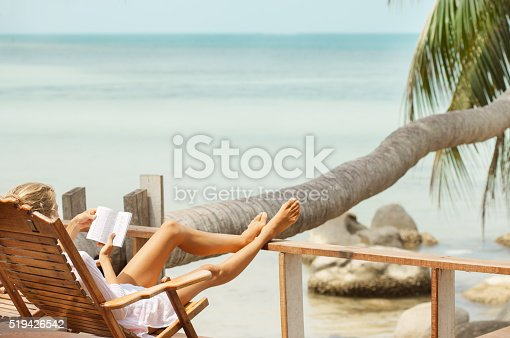 538041934 istock photo Young woman reading a book while relaxing on tropical island 519426542