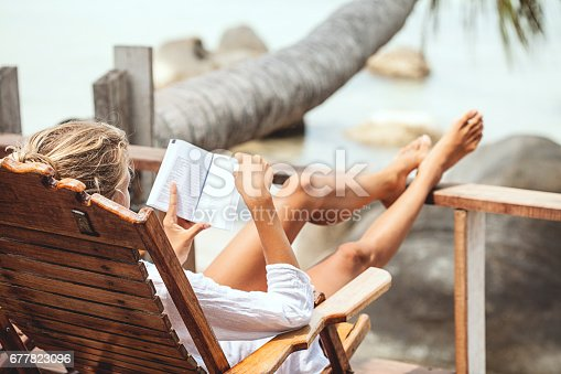 istock Young woman reading a book while relaxing on tropical island 677823096