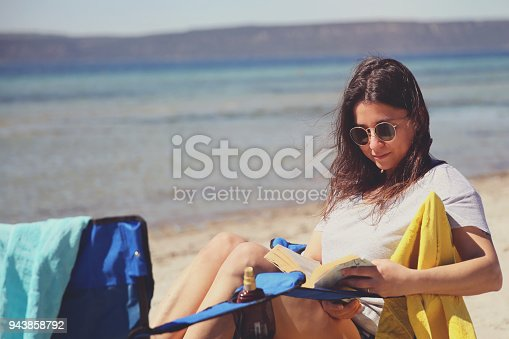538041934 istock photo Young woman reading a book while relaxing on tropical island 943858792