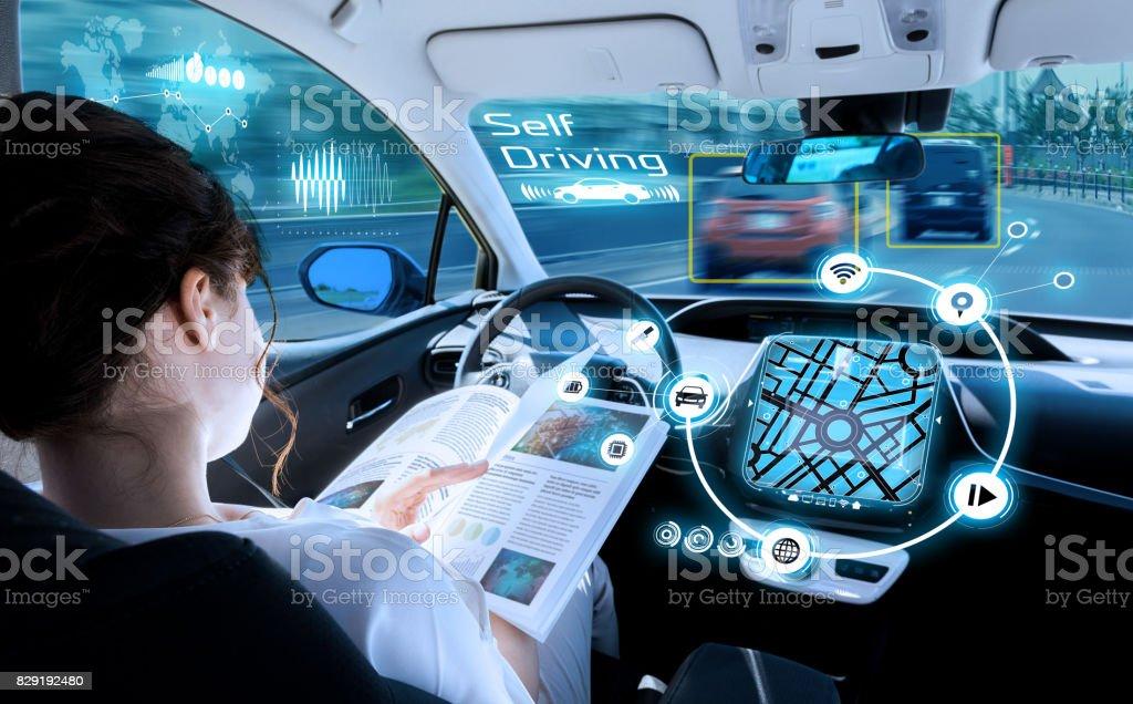 ung kvinna läser en tidning i en autonom bil. förarlös bil. självkörande fordon. Heads-up display. fordonsteknik. bildbanksfoto