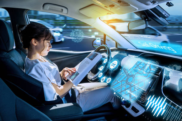 young woman reading a magazine in a autonomous car. driverless car. self-driving vehicle. heads up display. automotive technology. stock photo