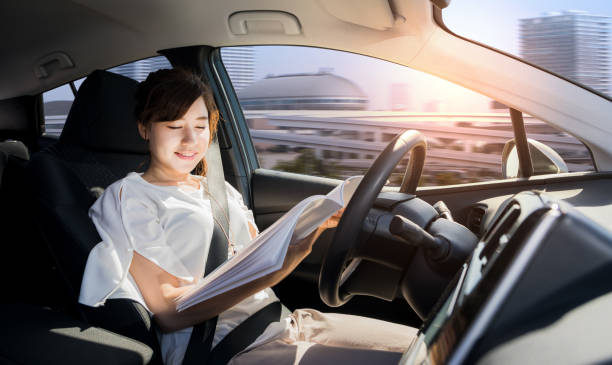 young woman reading a magazine in autonomous car. self driving vehicle. autopilot. automotive technology. stock photo
