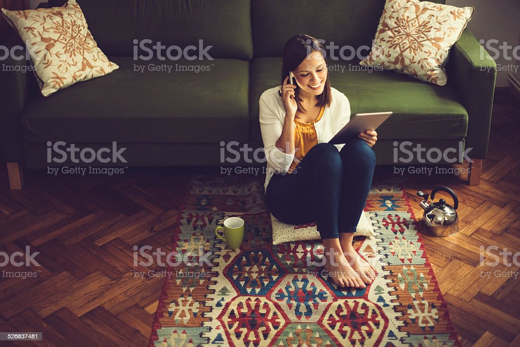 Young woman reading a tablet and listening her messages stock photo