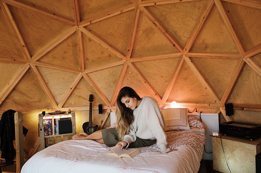 Young woman reading and lying on bed inside a cozy wooden dome