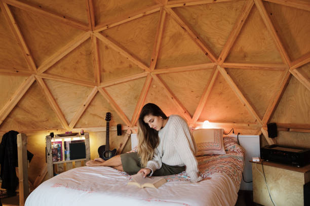 Young woman reading and lying on bed Young woman reading and lying on bed inside a cozy wooden dome image stock pictures, royalty-free photos & images