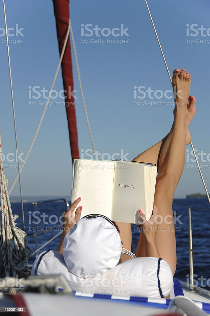 Young woman reading and sunbathing on sail boat royalty-free stock photo
