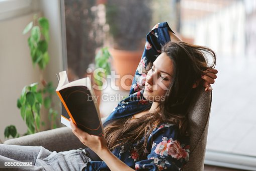 Vintage toned portrait of a young woman relaxing and reading after work, in the bright and beautiful apartment on the high floor in Belgrade, Serbia. She is wearing casual, everyday clothes.