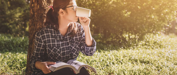 junge Frau Buch lesen und Kaffee aus der Tasse trinken. – Foto