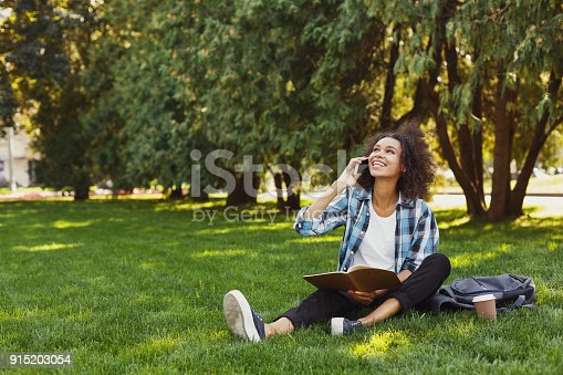 1009493672istockphoto Young woman reading book and talking on phone 915203054