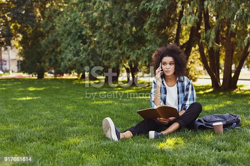 1009493672istockphoto Young woman reading book and talking on phone 917661614
