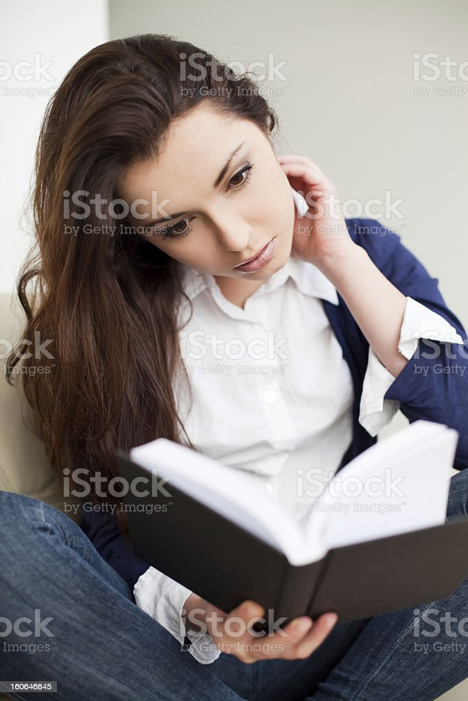 Young woman reading book at home royalty-free stock photo
