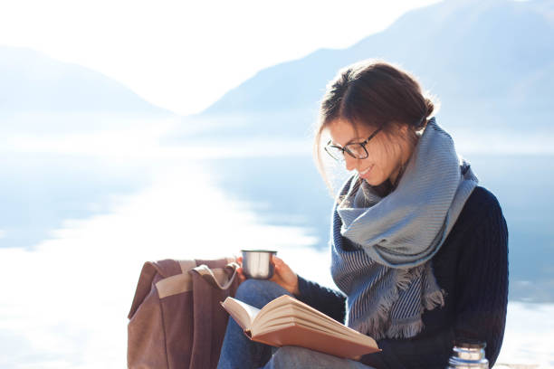 Young woman reading book at sea beach. Cozy winter picnic by morning mountains. Happy student stock photo