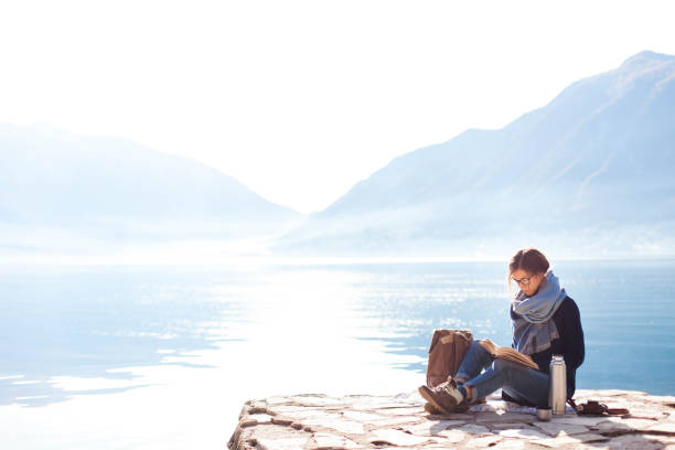 Young woman reading book at sea beach. Cozy winter picnic by morning mountains. stock photo