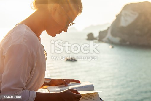 Young woman reading book at sunset in front of the sea on Ponza island coast, sitting on a wall with view of the ocean. 9759