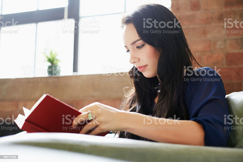 Young woman reading book in armchair. - Royalty-free 25-29 Years Stock Photo