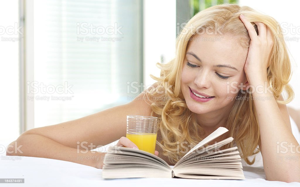 young woman reading book in bed royalty-free stock photo