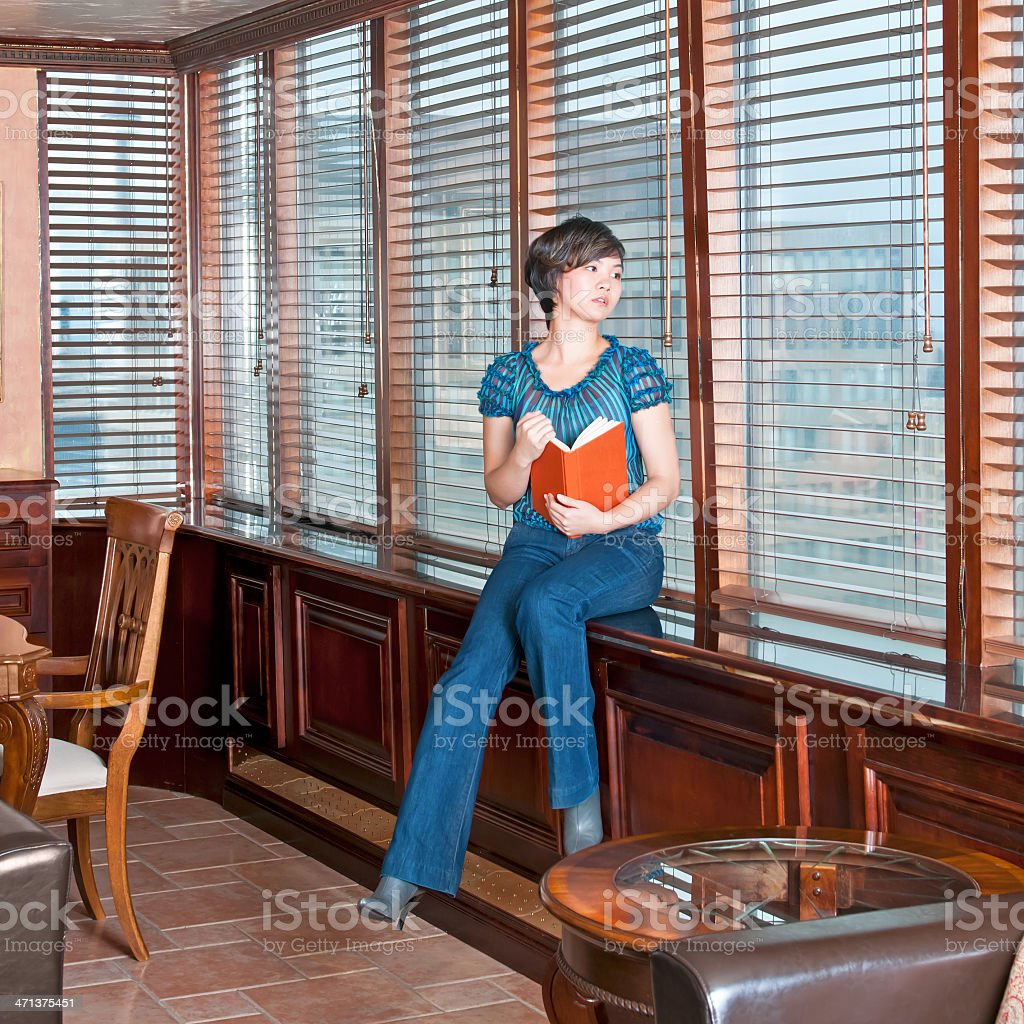 Young woman reading book in her city condo - IV royalty-free stock photo