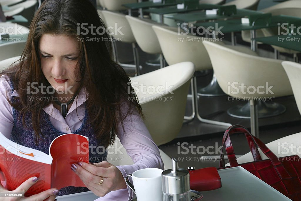 Young woman reading book in modern cafe royalty-free stock photo