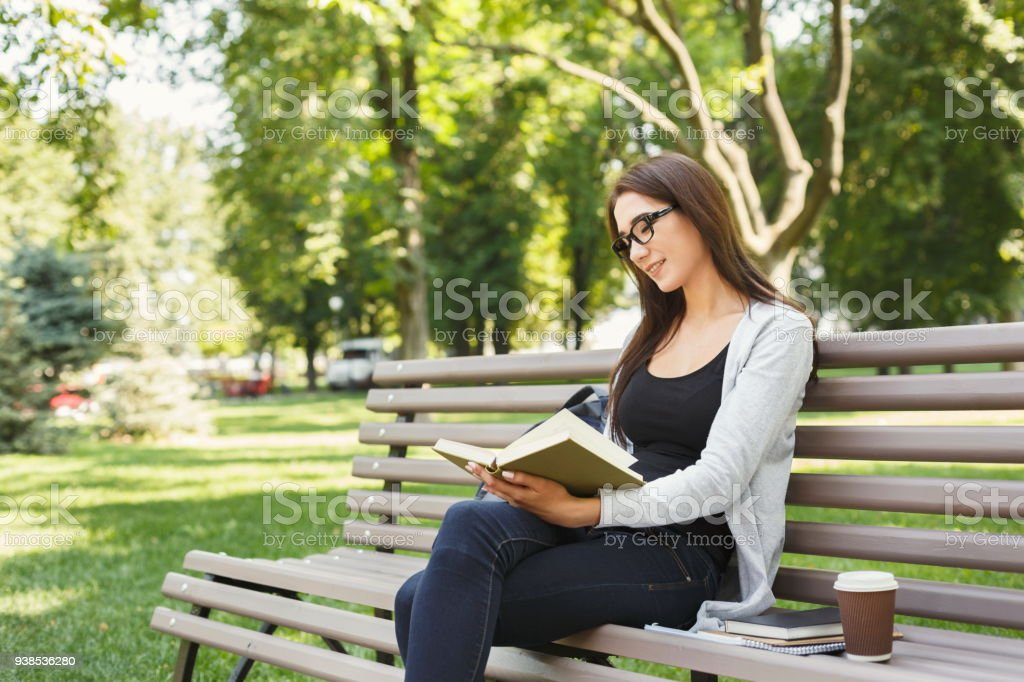 Young woman reading book in park copy space stock photo