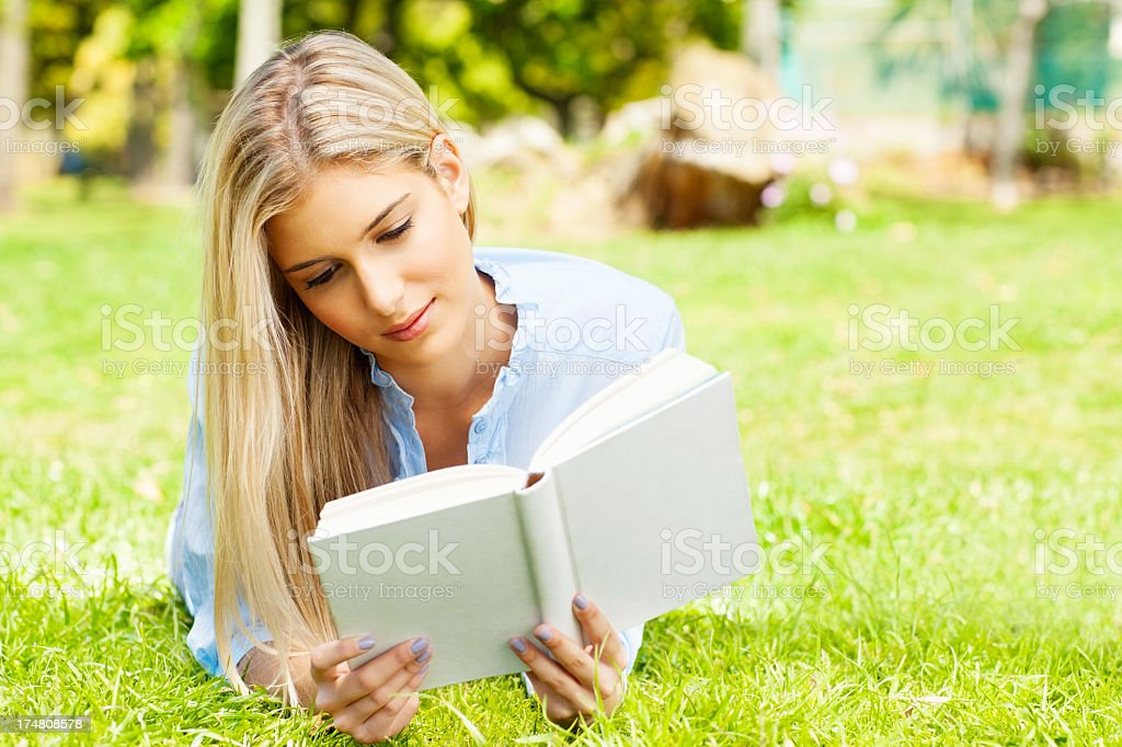 Young Woman Reading Book In Park royalty-free stock photo