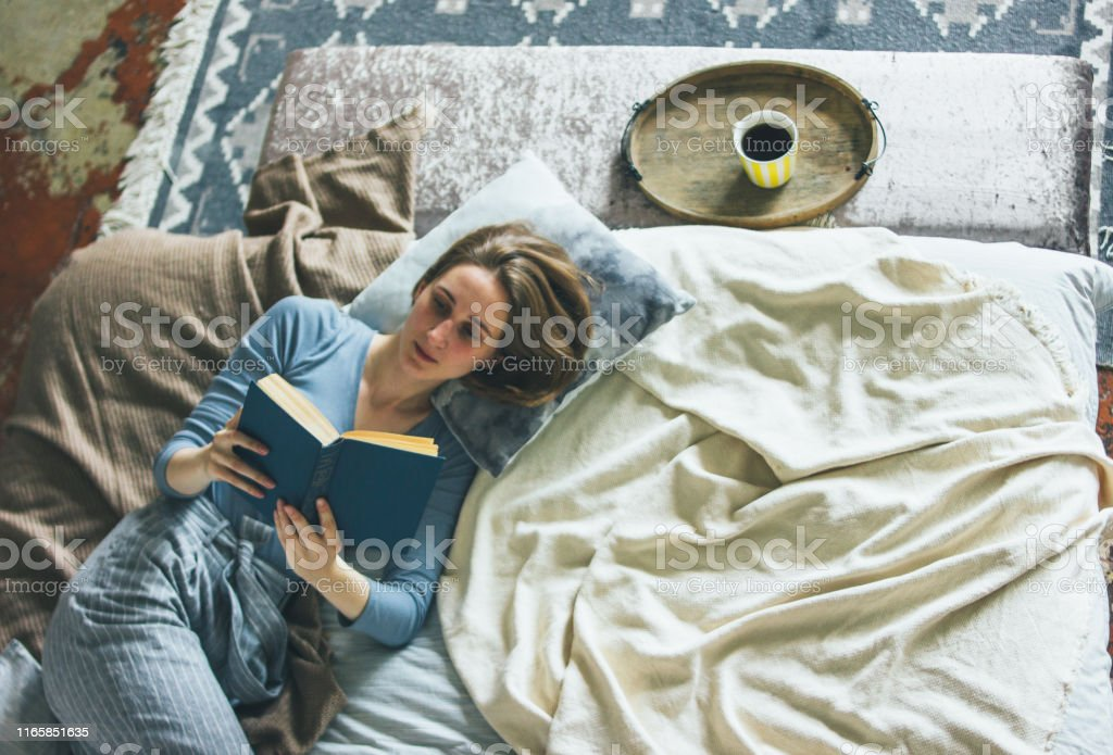Young woman reading book on bed in the loft room, slow life