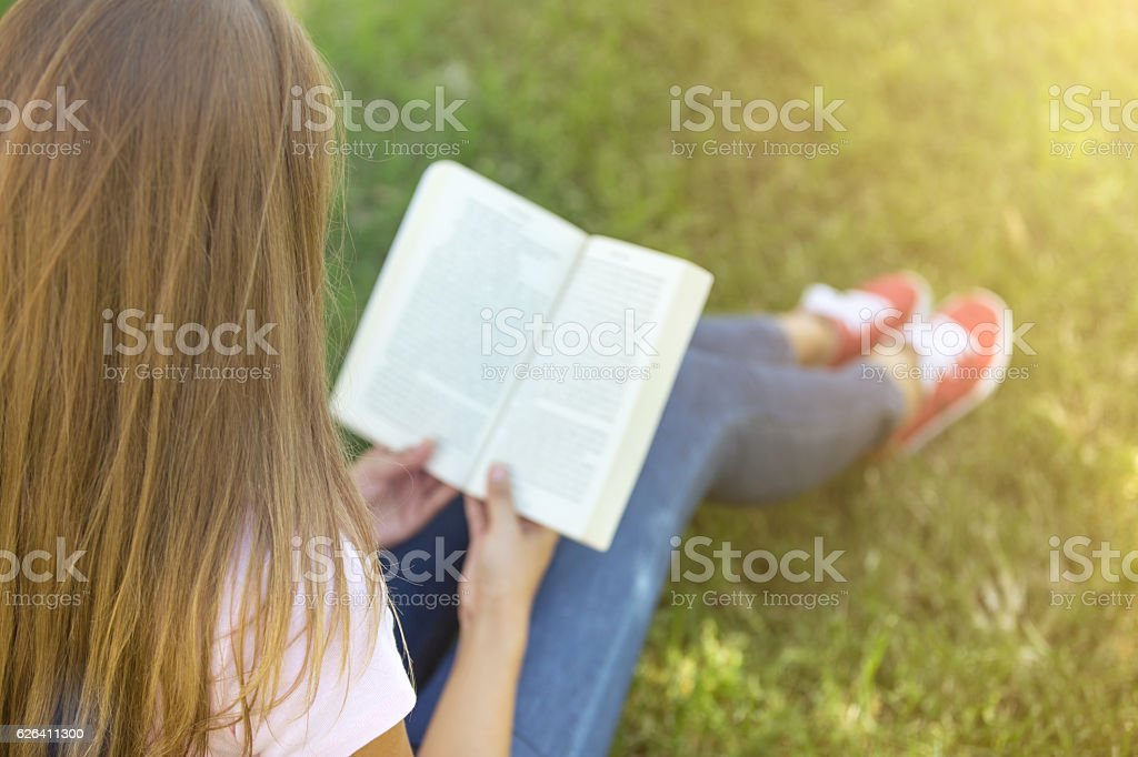 Young woman reading book on the grass stock photo