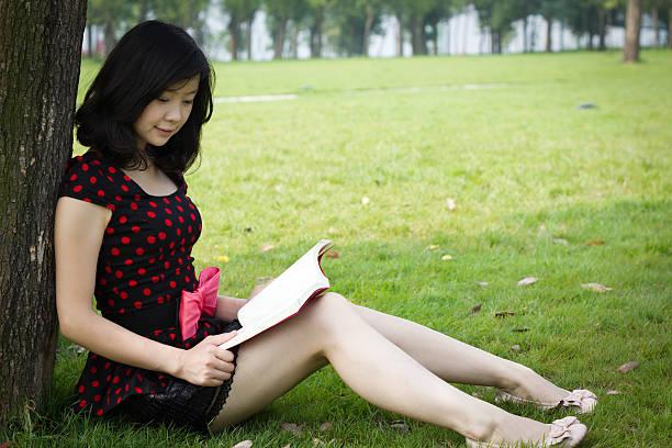 junge frau liest buch - pengpeng stock-fotos und bilder