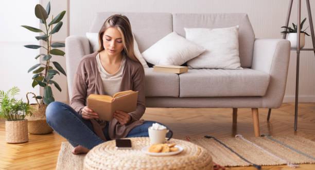 Junge Frau lesen Buch, sitzen auf dem Boden zu Hause – Foto