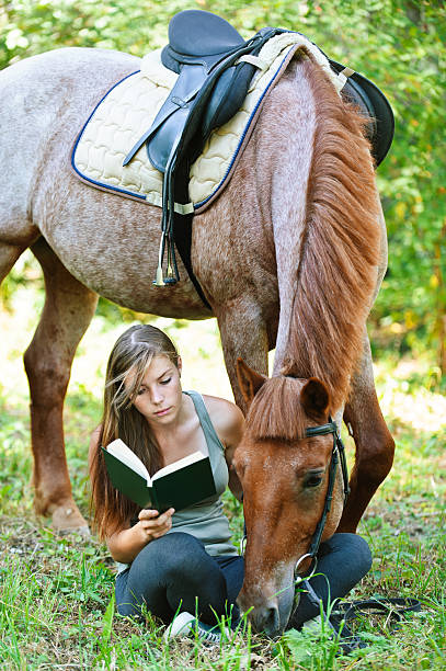 young woman reading book with horse stock photo