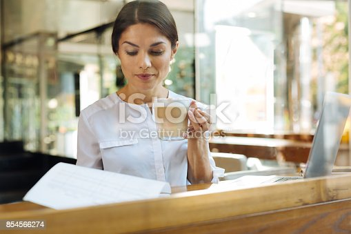 istock Young woman reading contract while drinking latte 854566274