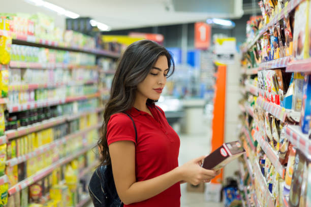 Young woman reading food labels Young woman reading food labels discount store stock pictures, royalty-free photos & images