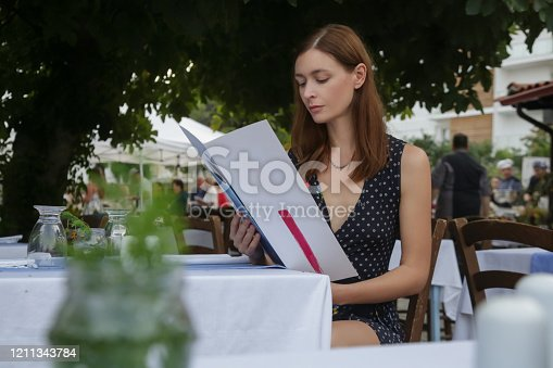 Young woman reading food menu at the outdoor restaurant