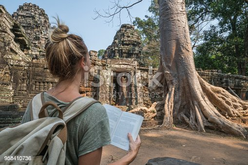 Young woman traveling in Cambodia visiting the temples of Angkor wat complex and reading guidebook. People travel discovery Asia concept. Shot at sunset, one woman only, adventure and exploration in Siem Reap, Southeast Asia.