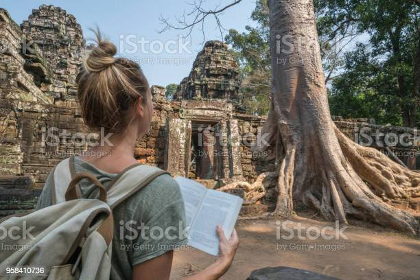 Young woman reading guidebook at ancient temple in cambodia picture id958410736?b=1&k=6&m=958410736&s=612x612&h=5tca6yp0kxpyr9tx7chchsea1l1gzaslvqic69lukyu=