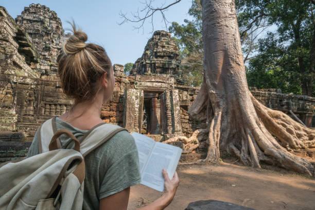 Junge Frau lesen Ratgeber im alten Tempel in Kambodscha – Foto