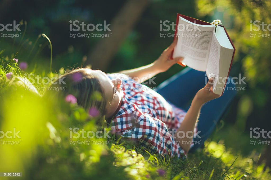 Young woman reading in the garden stock photo