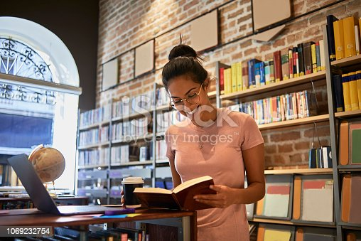 istock young woman reading in the library 1069232754