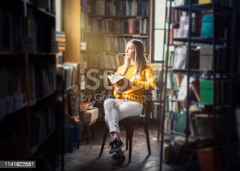 Young woman reading in the library with beautiful light from a window